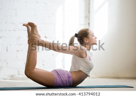 Beautiful young woman wearing casual clothing enjoying yoga indoors. Yogi girl working out in sunny loft interior. Doing Dhanurasana, Bow Pose. Full length - stock photo