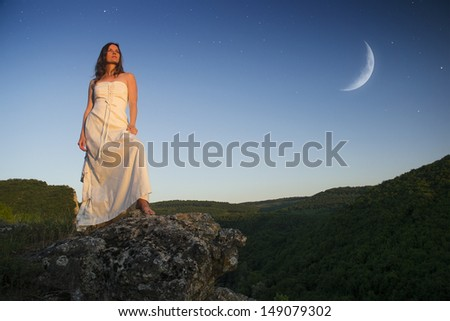 Beautiful young woman wearing elegant white dress standing on a rock overlooking the great expanse of forests and mountains under blue sky with moon and stars - stock photo