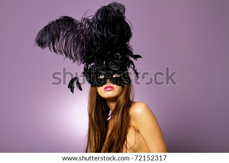Beautiful young woman wearing fashionable carnival mask