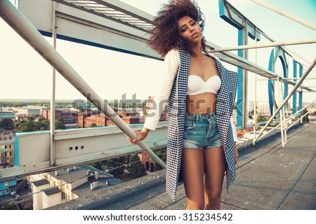 Beautiful young woman wearing fashionable clothes posing on the rooftop. Fashion look photo. Afro hairstyle - stock photo
