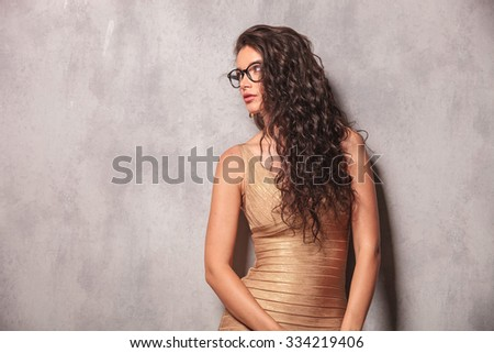 beautiful young woman wearing glasses pose looking away with her hands down - stock photo
