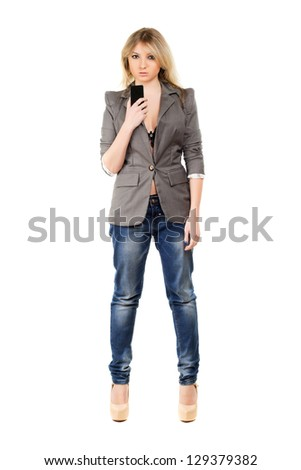 Beautiful young woman wearing grey jacket and blue jeans with a mobile phone. Isolated on white - stock photo