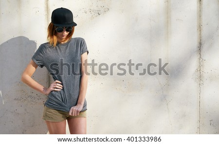 beautiful young woman wearing in a gray blank t-shirt and black blank cap posing against a background of a concrete wall in the rays of the setting sun - stock photo