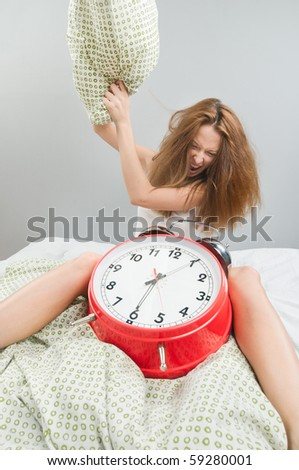 Beautiful young woman wearing lingerie in bed with alarm clock