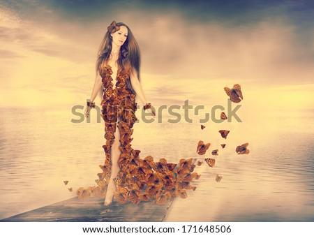 Beautiful young woman wearing orange butterflies dress - stock photo