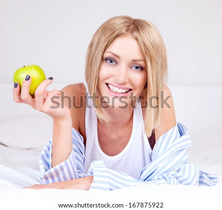 beautiful young woman wearing pajamas eating an apple in bed at home - stock photo