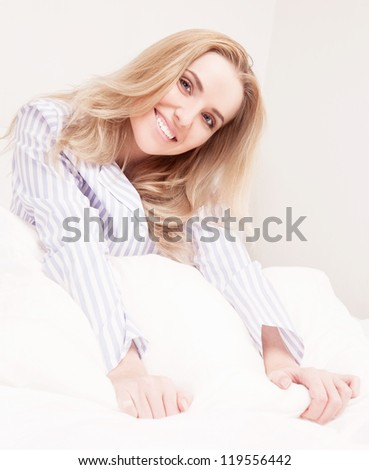 beautiful young woman wearing pajamas waking up and stretching  in bed at home - stock photo