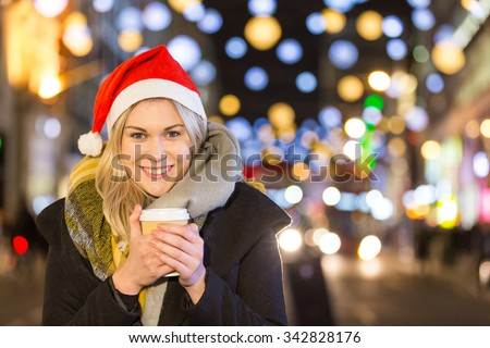 Beautiful young woman wearing Santa hat in London. She is blonde, on her early twenties, holding a cup of coffee and wearing warm clothes. On background there are many Christmas lights. - stock photo