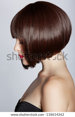 beautiful young woman wearing short bob hairstyle on studio background - focus on the eyes - stock photo