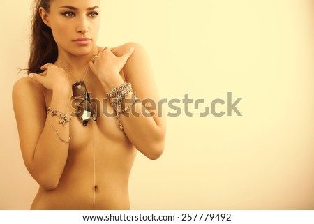 beautiful young woman wearing silver sunglasses and jewelry, studio shot