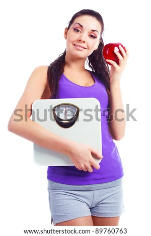 beautiful young woman wearing sports clothes holding scales and eating an apple, isolated against white background