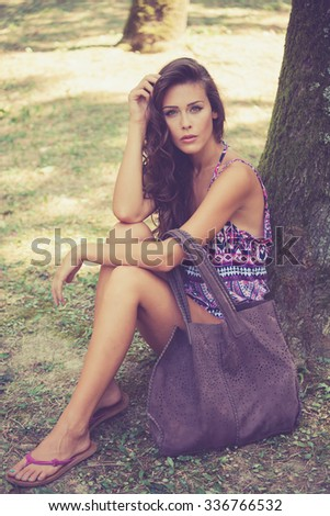 beautiful young woman wearing thongs and  summer clothes with leather bag sit by tree in wood, full body shot, look at camera, summer day