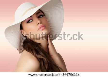 beautiful young woman wearing white summer hat, studio - stock photo