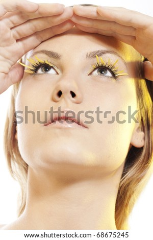 Beautiful young woman wearing yellow petal eyelashes