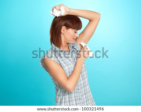 beautiful young woman, wiping her armpit sweat with napkins, on blue background