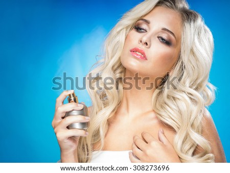 Beautiful young woman with a bottle of perfume - stock photo