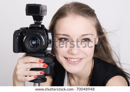 Beautiful young woman with a camera in his hands.