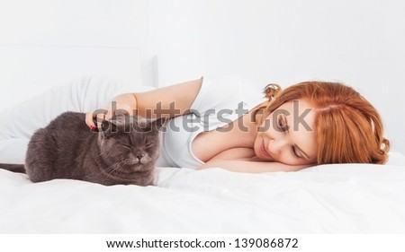 beautiful young woman with a cat in bed at home
