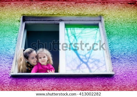 Beautiful young woman with a child of five years old look out of the window and welcome - stock photo