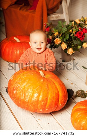 Beautiful young woman with a child on the front porch with pumpkins autumn. Smiling mother and son.