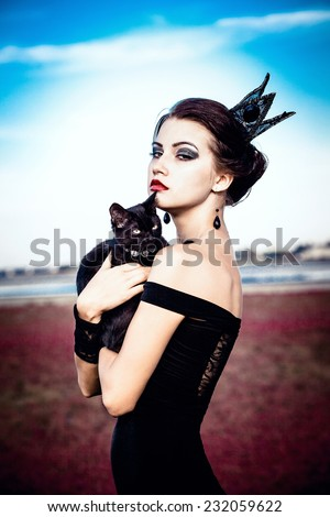 Beautiful young woman with a crown on her head, holding a black cat on her arms. - stock photo