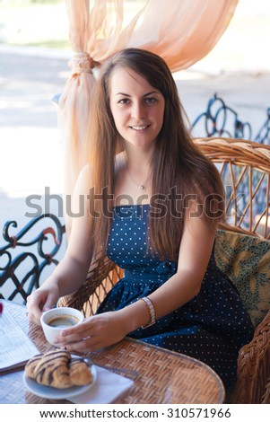 Beautiful young woman with a cup of coffee at a cafe