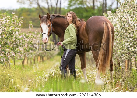 Beautiful young woman with a horse in blooming orchard. - stock photo