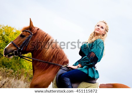 Beautiful young woman with a horse outdoor. The end of summer and beginning of autumn. Beautiful and colorful landscape. Girl riding the stallion in the field. Hippotherapy