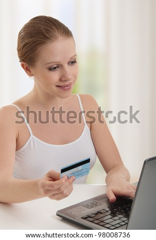 beautiful young woman  with a laptop makes a payment online using credit cards at home