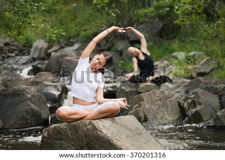 Beautiful young woman with a man behind meditating in yoga pose at a mountain stream. Selective focus on woman. - stock photo