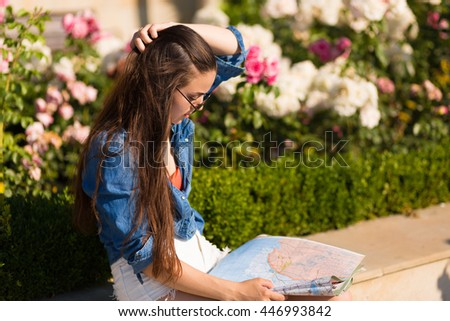 Beautiful young woman with a map on vacation in the summer city