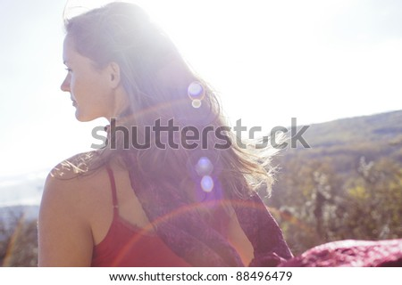 Beautiful young woman with a red dress looking in the distance - stock photo