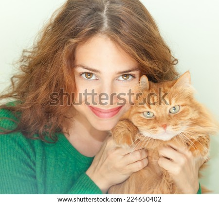 beautiful young woman with a red fluffy cat - stock photo