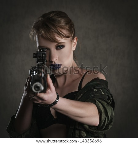 Beautiful young woman with a rifle against dark background - stock photo