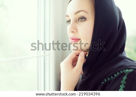 Beautiful young woman with a scarf at home - stock photo