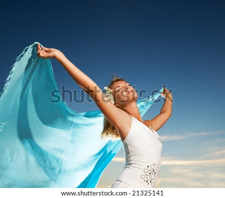 Beautiful young woman with a shawl relaxing outdoors - stock photo
