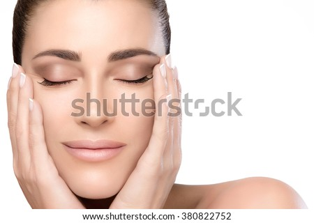 Beautiful young woman with a smooth unblemished complexion, hands on cheeks and eyes closed with a serene expression in a beauty, skincare and spa concepts. Perfect skin. Portrait isolated on white - stock photo
