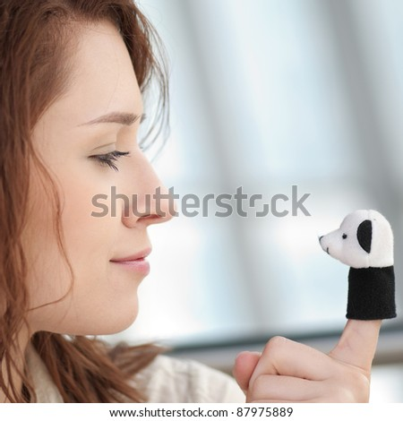 Beautiful young woman with a toy bear indoor. Love - stock photo