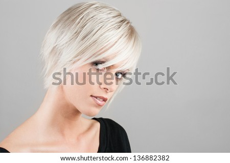 Beautiful young woman with a trendy blonde hairstyle, head and shoulders portrait on a grey studio background - stock photo