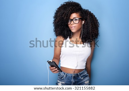 Beautiful young woman with afro listening to music from mobile phone. Studio shot. Blue background. - stock photo