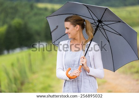 beautiful young woman with an umbrella outdoors - stock photo