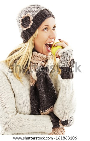 Beautiful young woman with apple, looking up. Winter style. Isolated on white background  - stock photo