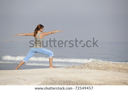 Beautiful young woman with arms open, relaxing on the beach - stock photo