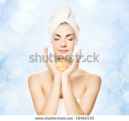 Beautiful young woman with aroma bath ball over abstract blurred background - stock photo