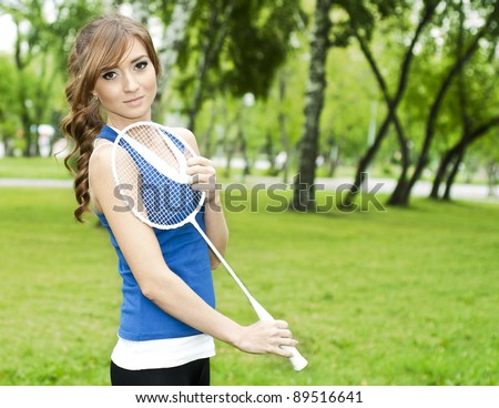 Beautiful Young Woman with Badminton racket, in the summer park - stock photo