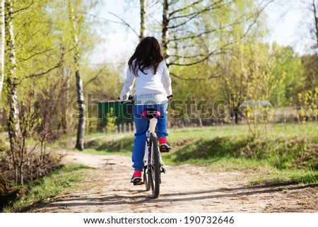 beautiful young woman with bicycle in spring forest - stock photo