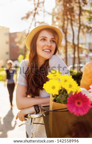 Beautiful young woman with bicycle with flowers in basket enjoying spring time. - stock photo