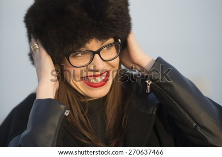 Beautiful young woman with big fur hat having fun on a sunny winter day. - stock photo
