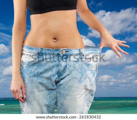 Beautiful young woman with big jeans, isolated on white.Woman showing how much weight she lost. Healthy lifestyles concept. - stock photo