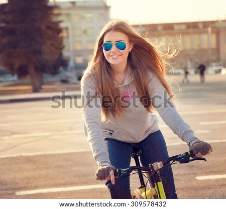 beautiful young woman with bike in the city - stock photo